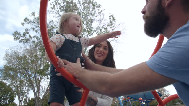 vídeos de stock, filmes e b-roll de cu young father playing with his daughter with down syndrome on a jungle gym - jungle gym