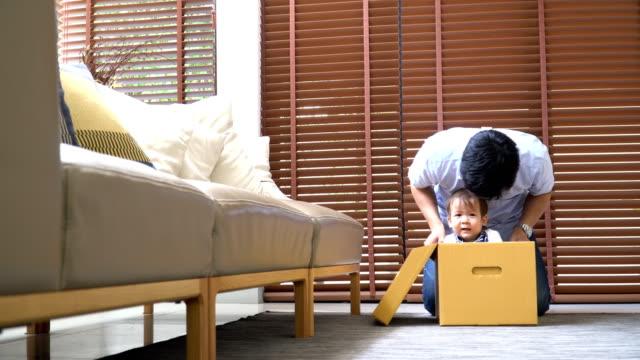 紙箱で息子と遊ぶ若い父親 - 生後18ヶ月から23ヶ月点の映像素材/bロール