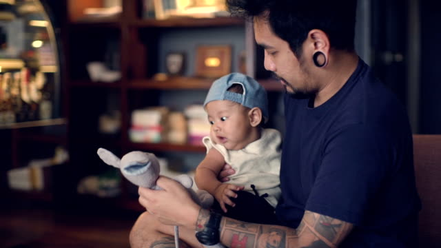 young father playing with son holding doll on sofa - doll stock videos and b-roll footage