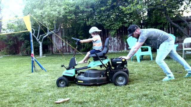 a young father pushes a riding lawnmower with his two year old son in the driver's seat in a cute moment of father son bonding time - tagliaerba video stock e b–roll
