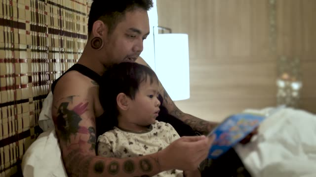 young father reads bedtime stories to his son in bed at home. - ora di andare a letto video stock e b–roll