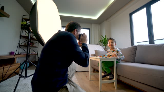 young father taking a photo of his son with camera at home for stock photography - 4 5 years stock videos & royalty-free footage
