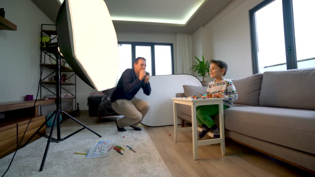 young father taking a photo of his son with camera at home for stock photography - filming stock videos & royalty-free footage