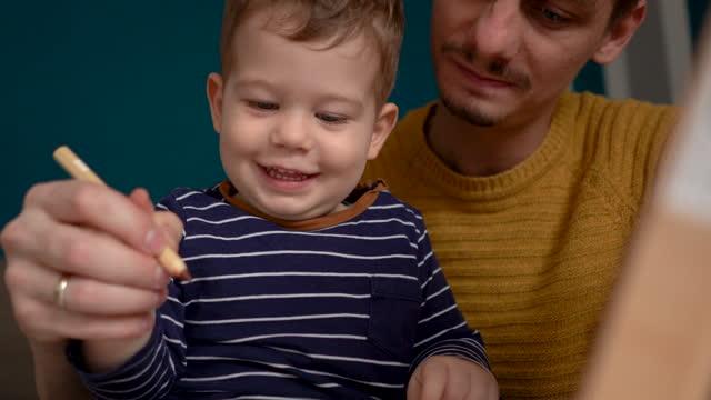 vídeos y material grabado en eventos de stock de joven padre enseñando a dibujar a su bebé - genderblend
