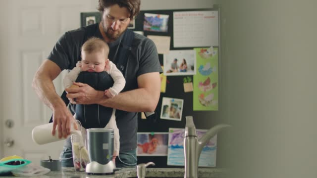 young father with child in front facing baby carrier pours milk while preparing healthy fruit smoothie in kitchen. - routine stock-videos und b-roll-filmmaterial