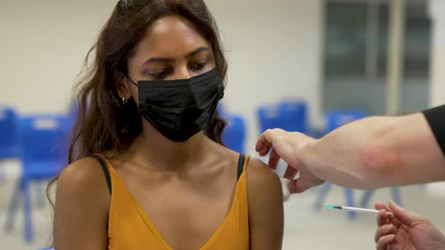 young female adult takes pfizer biontech vaccine as members of the public attend a mass vaccination centre in saxon court, milton keynes on july 23,... - young adult stock videos & royalty-free footage