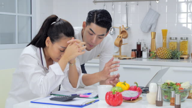 young female and her unemployed husband with many debts doing paperwork together in kitchen, reading notification.stressful moments - becco video stock e b–roll