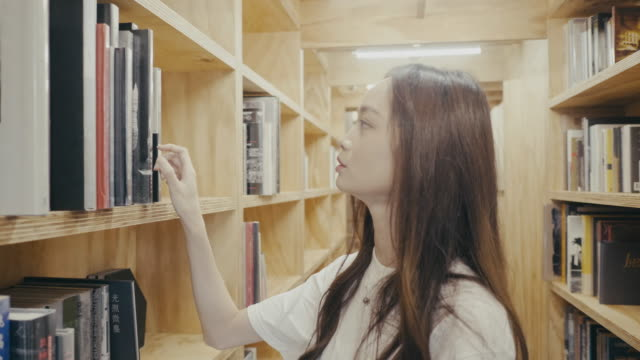 young female asian university student looks for a book in the library (slow motion) - book stock videos & royalty-free footage