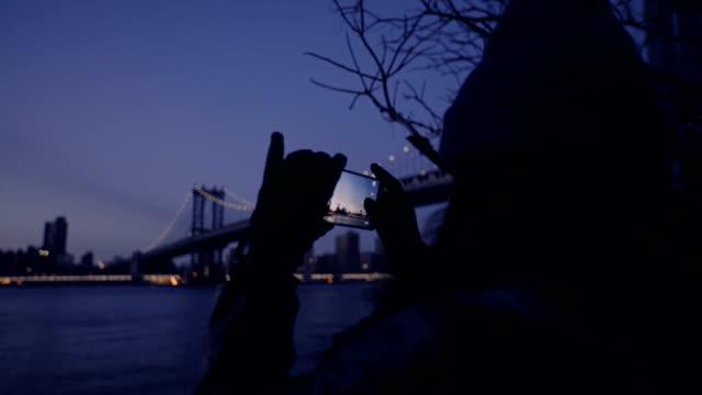 stockvideo's en b-roll-footage met jonge vrouw aan rivier fotograferen van brug met smartphone - portability