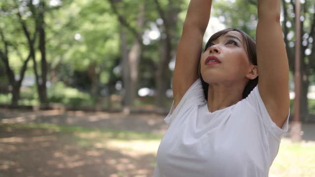 公共の公園で若い女性アスリートの深い破壊 - inhaling点の映像素材/bロール