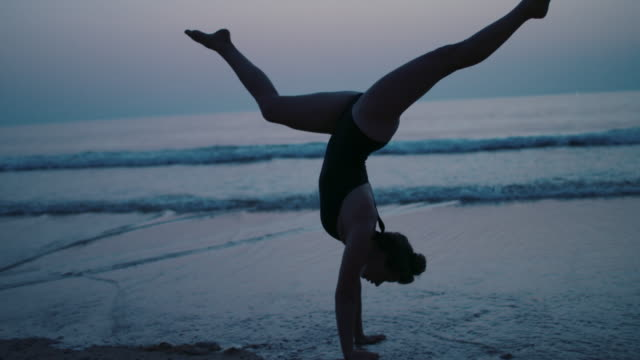 vídeos de stock, filmes e b-roll de young female athlete doing handstand on the beach after sunset - alegria