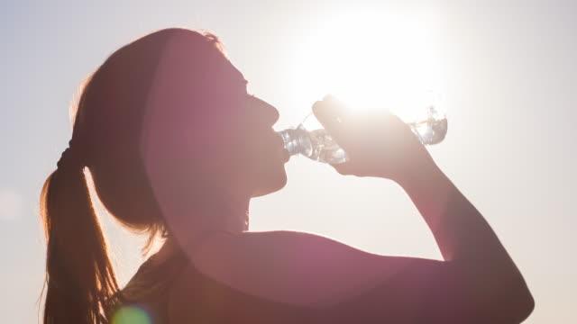 Jovem mulher água potável após treino de Fitness