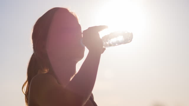 Young female athlete drinking water after working out