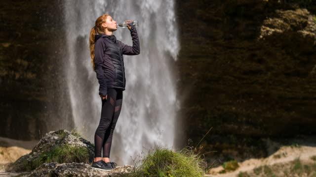 Joven atleta femenina agua potable frente a una cascada