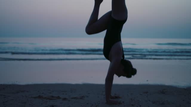 vidéos et rushes de young female athlete running and warming up outdoors after sunset - activité acrobatique