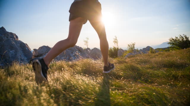Young female athlete running in the mountains at sunset