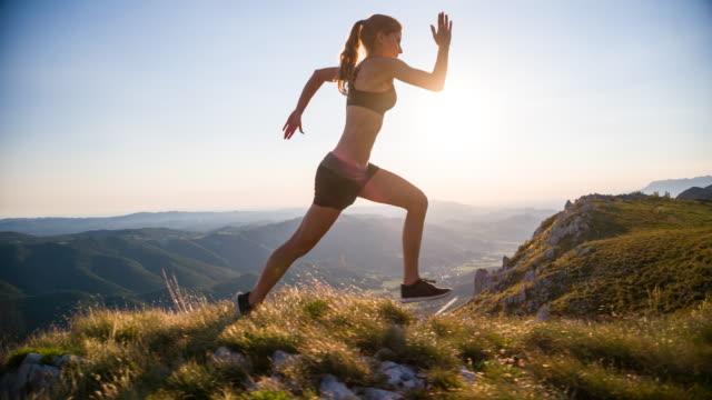 vídeos de stock, filmes e b-roll de jovem atleta feminina correndo nas montanhas - sutiã para esportes