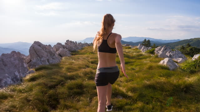 Junge Sportlerin, die auf einer Wiese in den Bergen