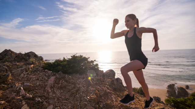 Young female athlete running on a rocky terrain by ocean