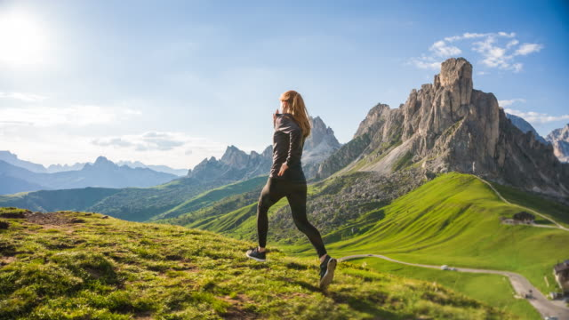Young female athlete running on grassy trails in mountain terrain