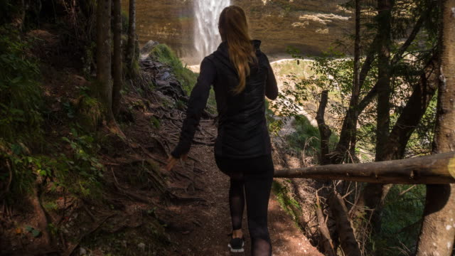 Young female athlete running through the woods towards a waterfall