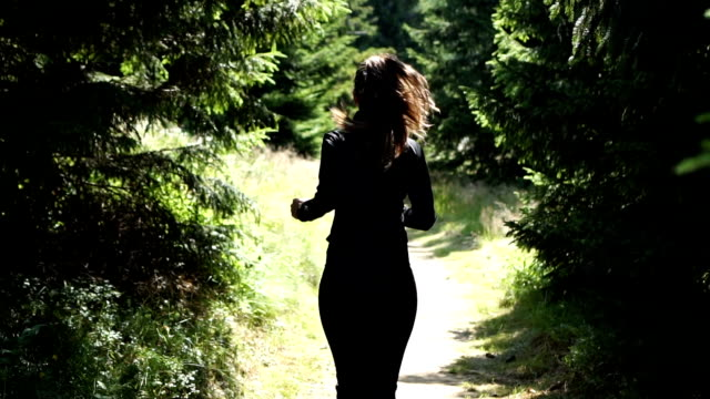 Young female athlete running through the woods