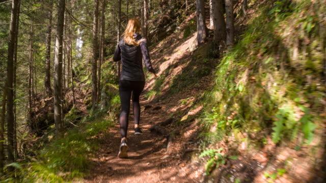 vídeos de stock, filmes e b-roll de jovem atleta feminina a correr pela floresta - outono