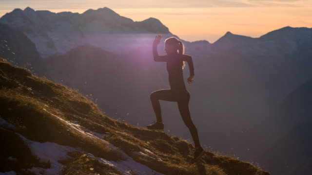 Young female athlete running up the mountain at sunset