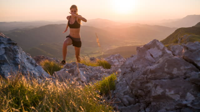young female athlete running up the mountain at sunset - conquering adversity stock videos & royalty-free footage