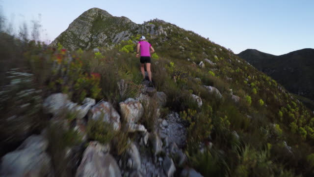 Young female athlete running up the mountain trail