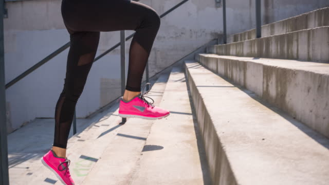 vídeos de stock e filmes b-roll de young female athlete running up the stairs - degraus