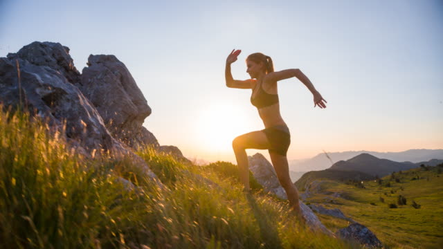 Young female athlete running uphill at sunset