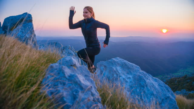 Young female athlete training in the mountains at dawn