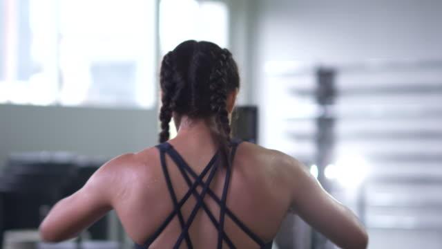 Young female athlete using exercising using rowing machine