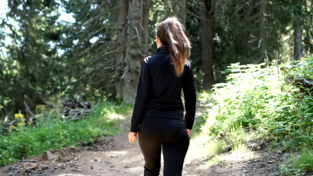 Young female athlete walking wooded trail