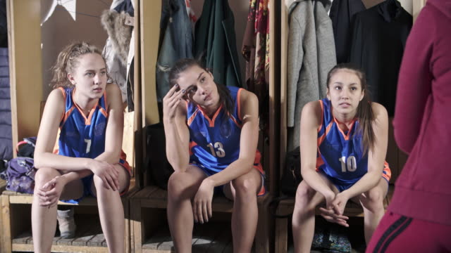 Young female athletes listening to basketball coach