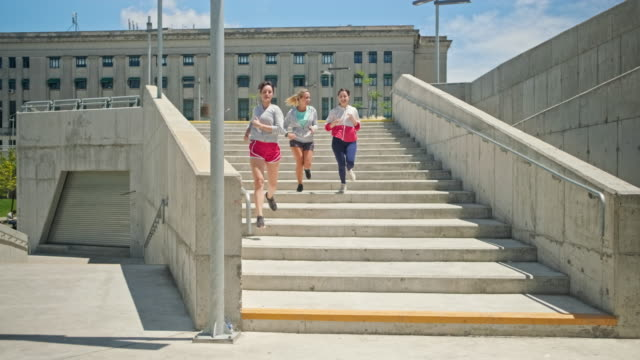 young female athletes running down the stairs in public park - mid distance stock videos & royalty-free footage