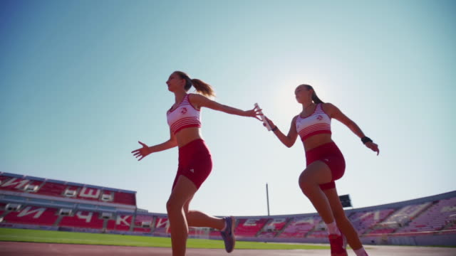 young female athletics exchanging relay baton - pista di atletica leggera video stock e b–roll