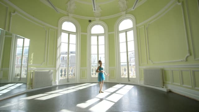 a young female ballet dancer glides and twirls across an open dancefloor - dance studio stock videos & royalty-free footage