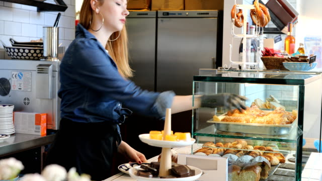 young female barista taking fresh baked bread - display cabinet stock videos & royalty-free footage