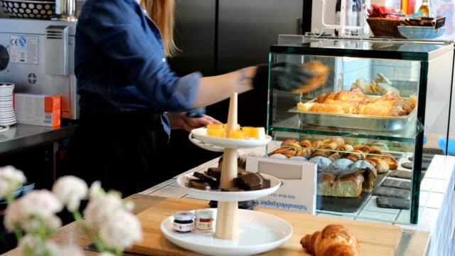 若い女性バリスタ取って新鮮な焼きたてのパン - 店頭点の映像素材/bロール