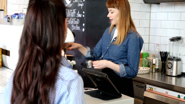 young female barista talking with customer at cafe - barista stock videos and b-roll footage