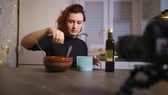 young female blogger salting salad while recording a tutorial - sich verschönern stock-videos und b-roll-filmmaterial