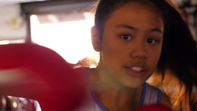 cu young female boxer boxing in ring during training session - 12歳から13歳点の映像素材/bロール