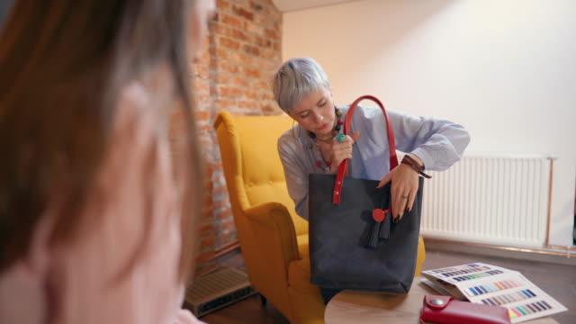 young female business owner explaining the bag design to her customer - strategia di vendita video stock e b–roll