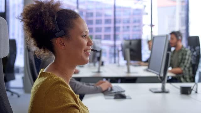 vidéos et rushes de jeune agent féminin de centre d'appel parlant à un client - centre d'appel