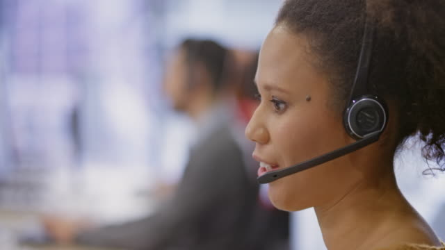 ld young female call centre agent talking with headphones - customer service representative stock videos & royalty-free footage