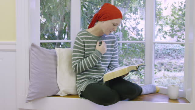 young female cancer patient holding bible - fatcamera stock videos and b-roll footage