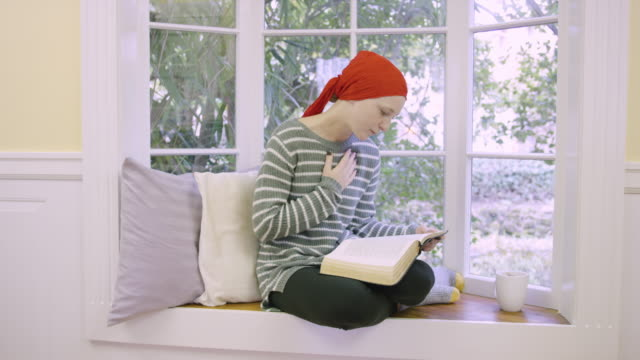 Young female cancer patient holding Bible