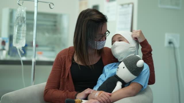 ung kvinnlig cancerpatient som sitter med sin mamma medan hon bar huvudduk och mask - cancer bildbanksvideor och videomaterial från bakom kulisserna